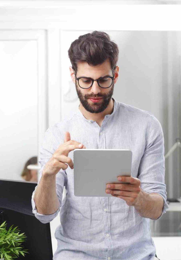 Junger Mann schaut am iPad nach Schadenersatzansprüchen