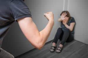 Mann schlägt mit seiner Faust auf einer in der Ecke sitzende, verängstigste Frau.