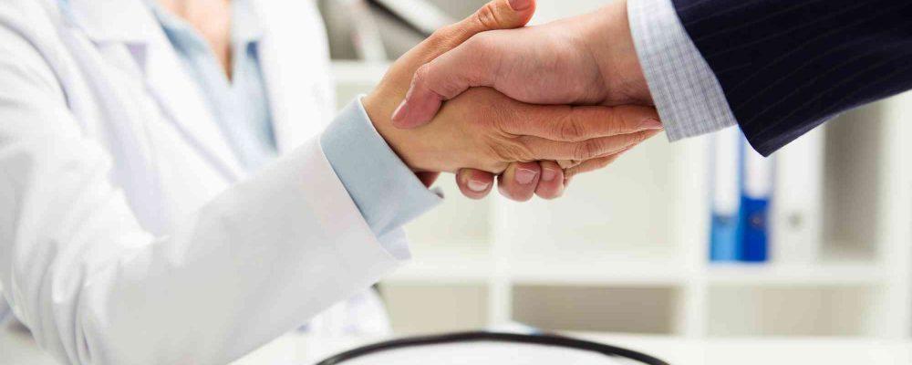 Ärztin reicht einem Patienten die Hand