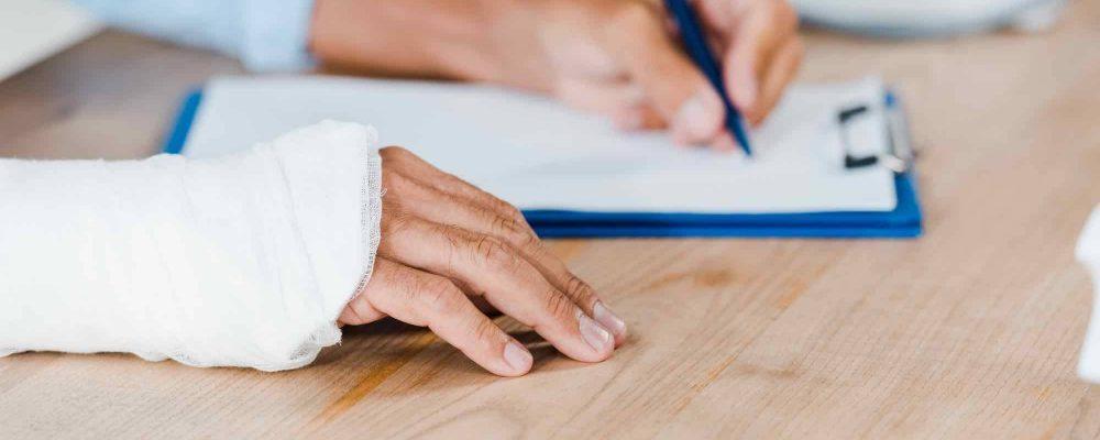 Mann mit Gibshand unterzeichnet Vertrag