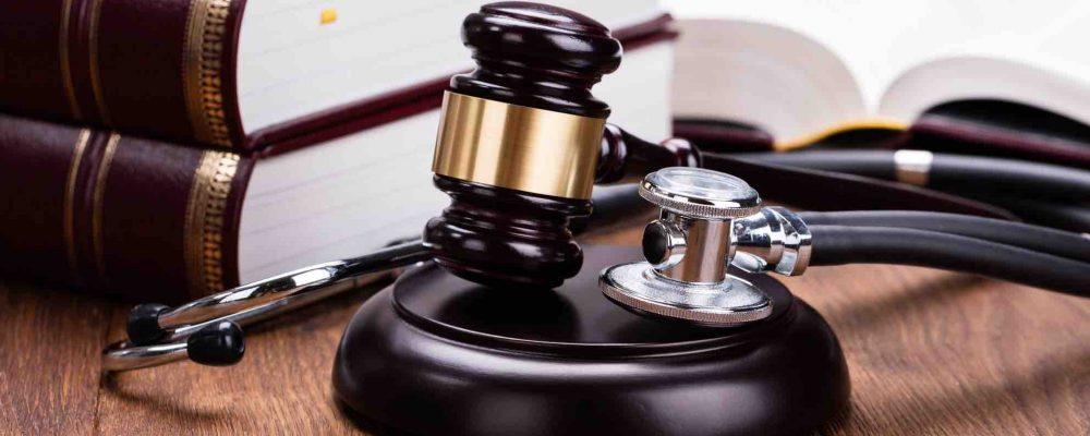 Gerichtshammer mit Stethoskop liegt am Tisch