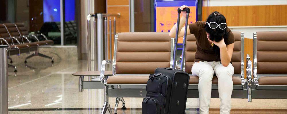 frau wartet genervt am Flughafen